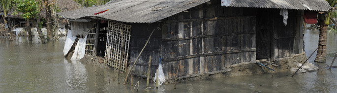 flooded area: water level is high and flooding wooden houses with tin roofs