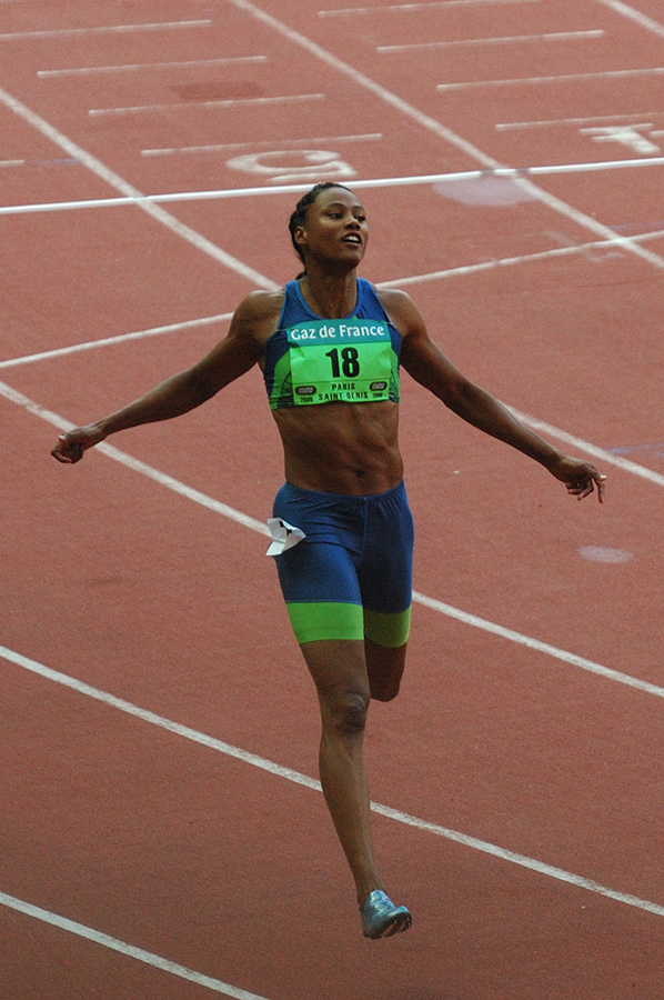 Lean, muscular black woman in blue/green cropped top and shorts after coming through the finish line, arms open