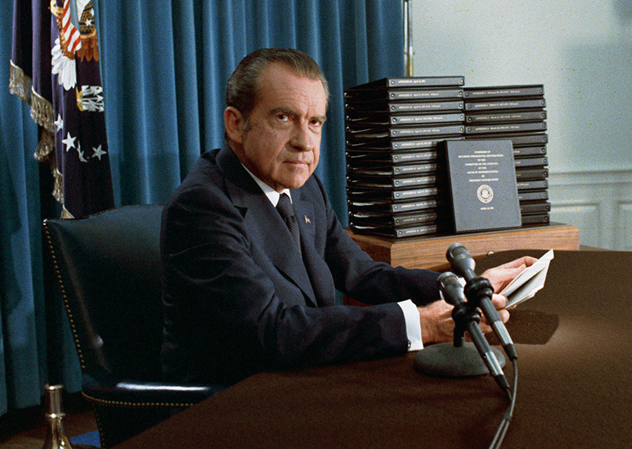 Nixon holding scripts, sitting in front of a desk