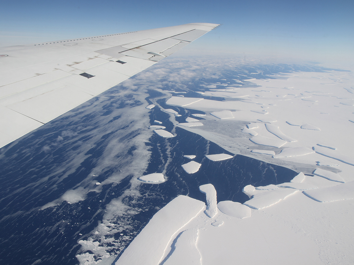 aerial view showing ice shelf calving into the ocean