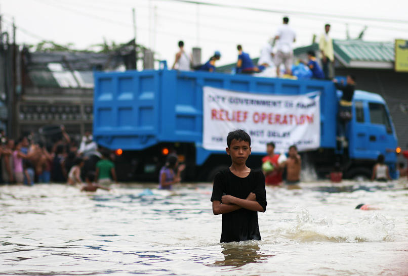 kid standing in waist-deep water with a relief truck in the background