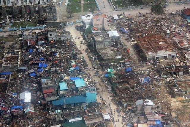 Scene of devastation with some flattened buildings and others without roofs.