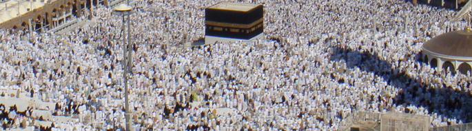Aerial view of millions of visitors packed together in mosque and dressed in white with crowded cityscape in background