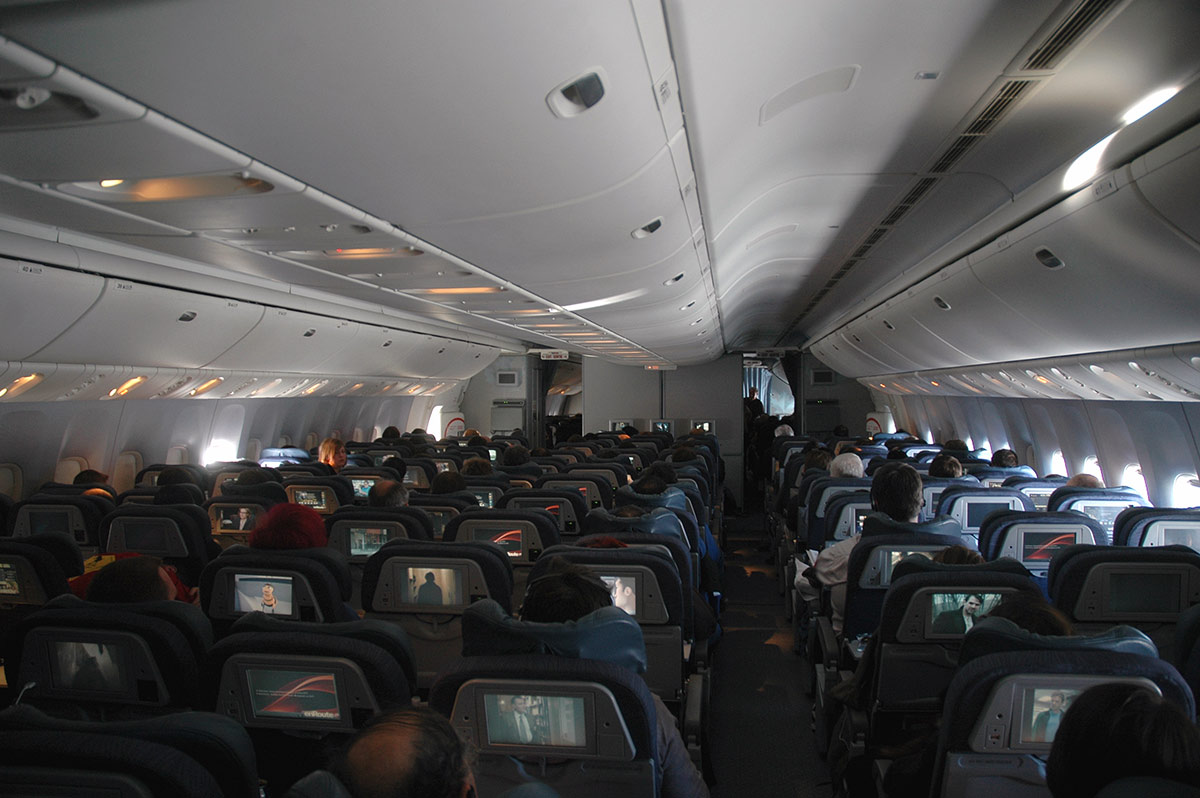 Photo of passengers in double-aisled airplane cabin; cabin about two-thirds full