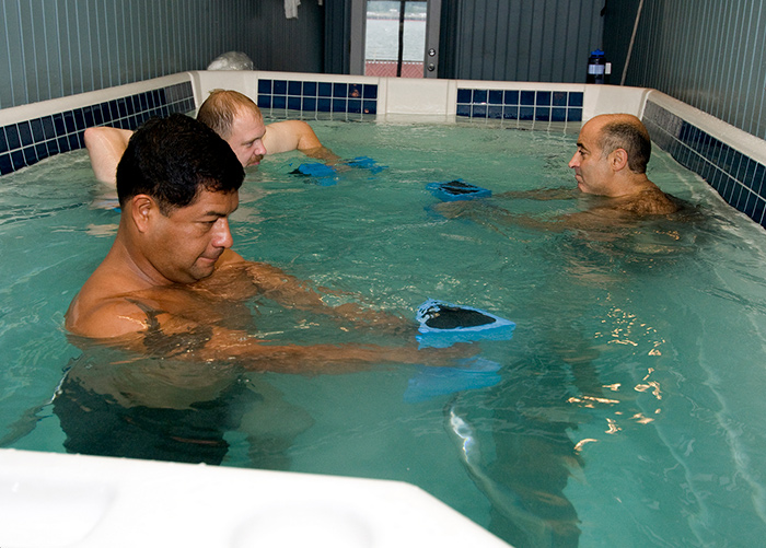 Three men in a square pool exercising and stretching with weights.