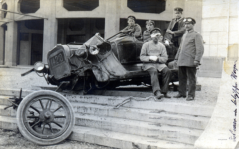 Old photo of mangled automobile, with front axle on the ground