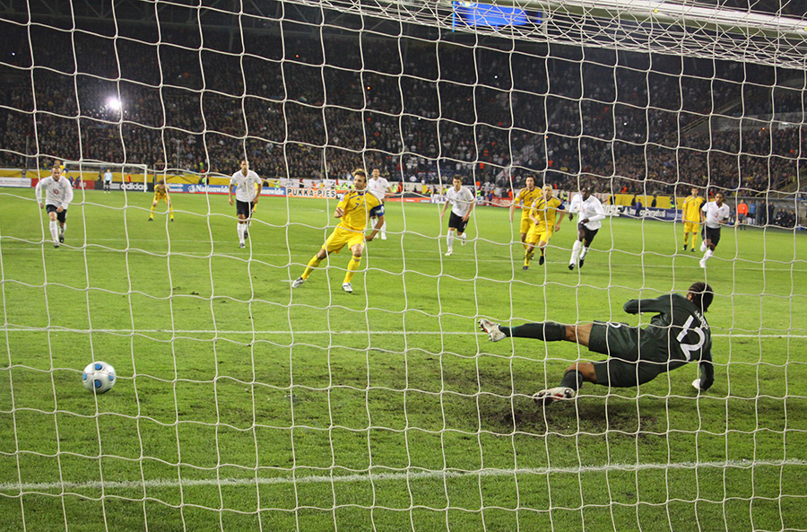 Photograph taken from behind soccer goal as a goalie dives away from a penalty shot.