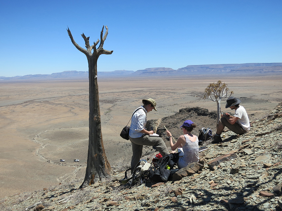 Photo of three researchers taking field observations on the dry, rocky landscape of Southern Namibia.