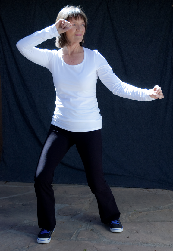 Woman calmly performing a tai chi pose.