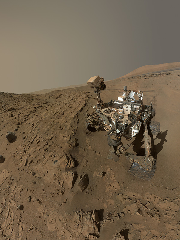 Photo of Curiosity on barren Mars landscape with dusty atmosphere. Wide wheels and a forest of instruments are seen.