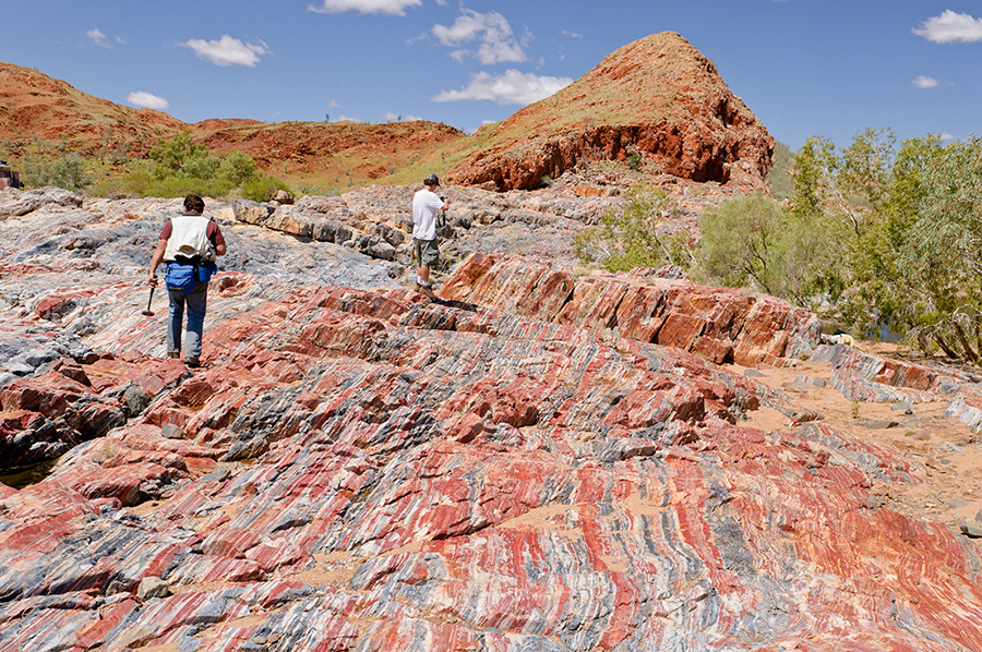 Photo of 2 geologists examining sedimentary rock in a scrubby, rocky landscape in Australia. Rock is banded ochre, gray and white.
