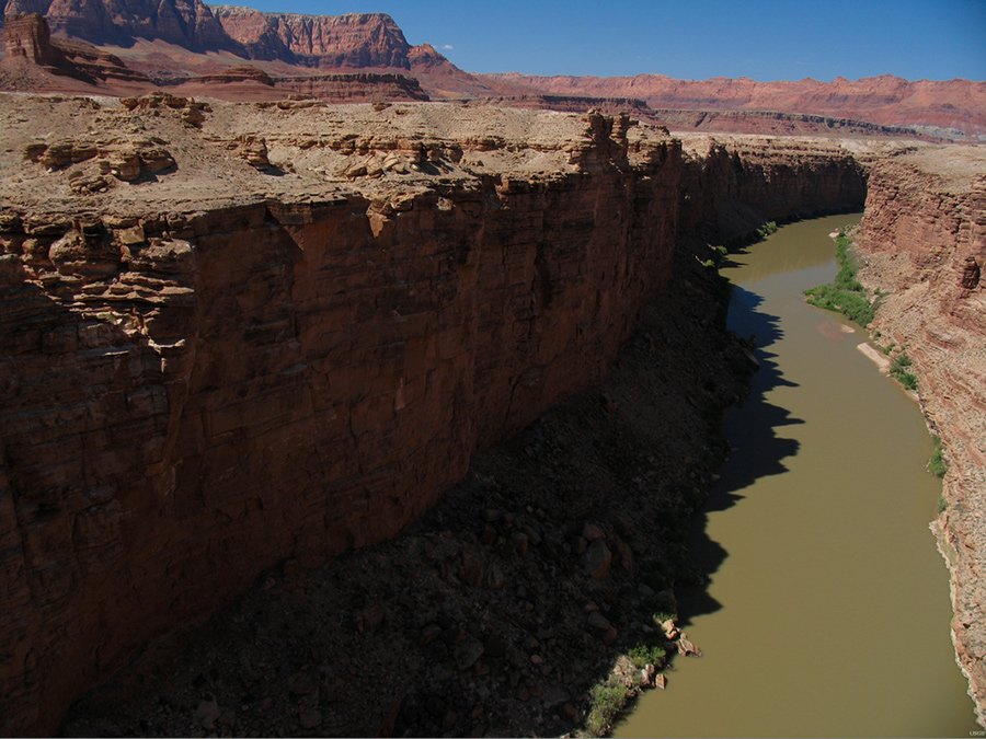 Photo of Colorado River in a deeply cut canyon with sharp, vertical cliffs.