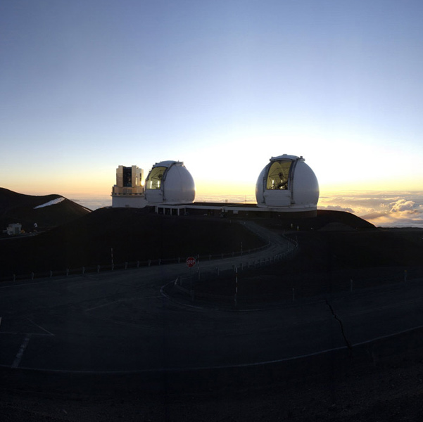 Photo of three domed observatories above the cloud layer at dusk.