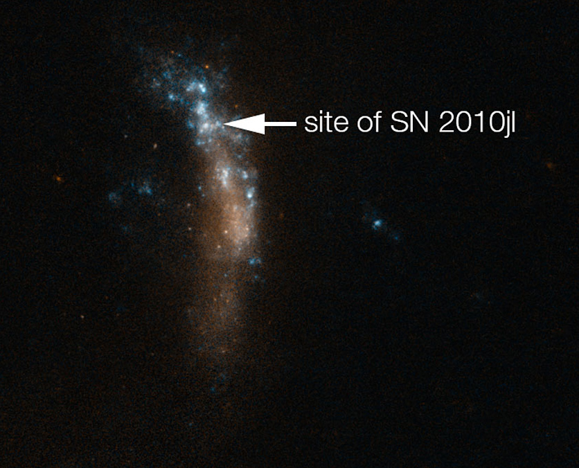 Vertical string of blue and red lights show a galaxy, with the supernova marked by arrow
