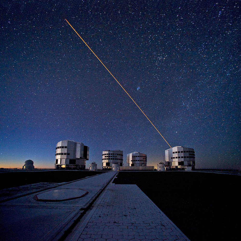 Four giant mushroom-shaped buildings at twilight; stars in background. Orange beam shines up toward space from one telescope