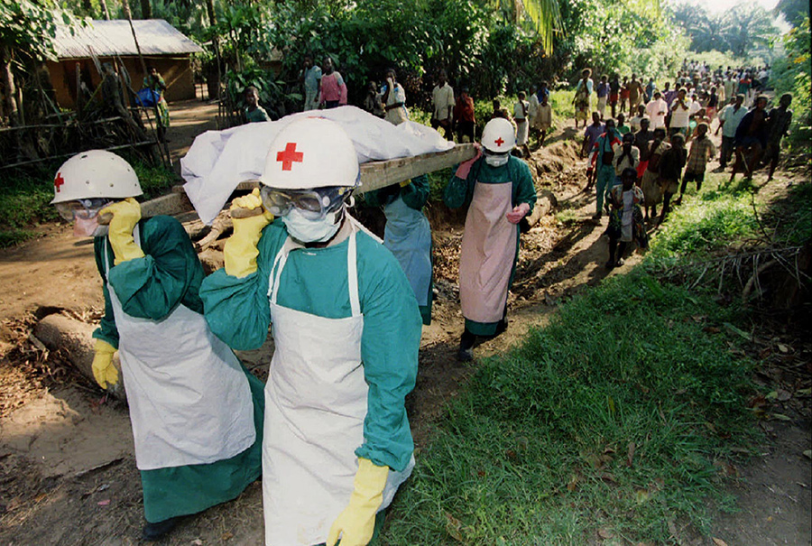 Photo of four red cross staffers cloaked in protective gear hoisting a body draped in white while a procession of villagers follows from a safe distance