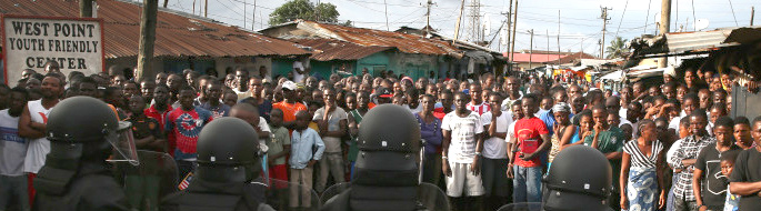 Photo of a tense standoff between Liberian police in riot-gear and around one hundred dismayed citizens