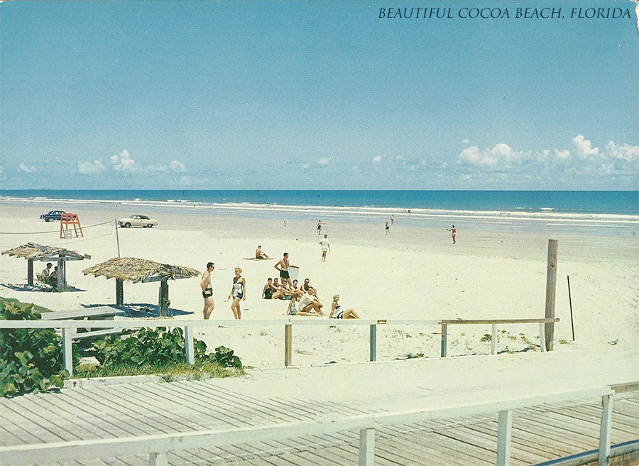 Postcard of a beach scene in Florida circa 1950; white sand, blue water and smiling beach-goers soaking up the sun