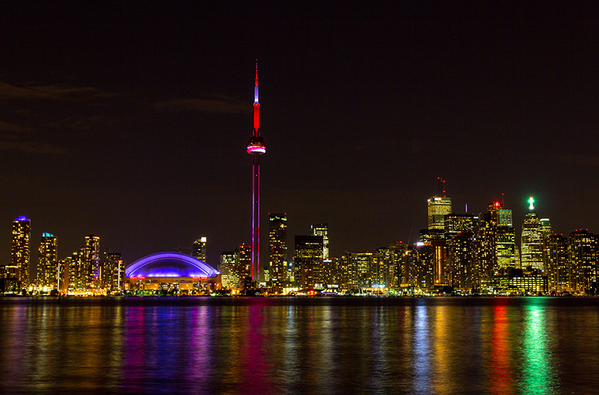 First image of brightly lit Toronto skyline at night; second shows buildings with lights turned out, including the iconic CN Tower.