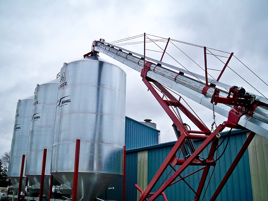 Photo of three bulk seed silos with a conveyor depositing seed into the top.