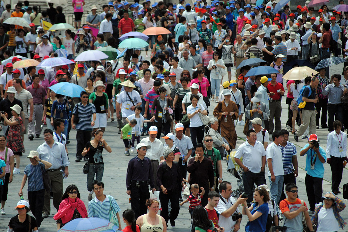 Photo of a crowded Beijing street scene packed with pedestrians.