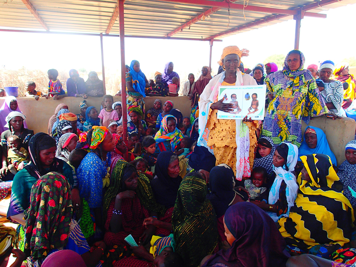 Colorfully-dressed West African women gather under a metal shelter; a standing woman holds an illustration on family planning.