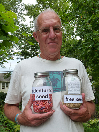 A satisfied man showcases two jars of seeds for the camera; one variety is labeled 'free,' the other 'indentured.'