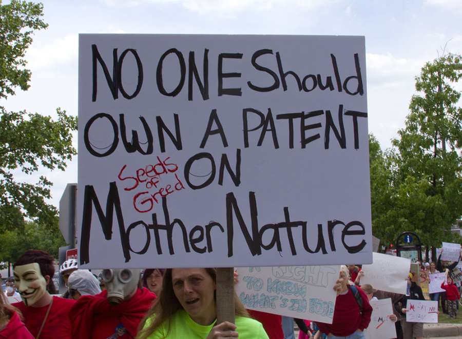 Photo of a woman holding a white sign that reads, 'No one should own a patent on Mother Nature.'