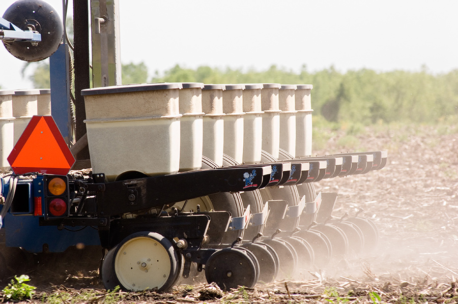 A seed-dropping trailer equipped with several jugs of soybeans is pulled across a plowed field.