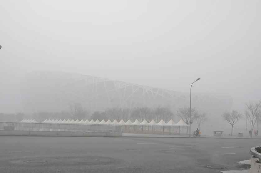 Photo of Olympic stadium which can hardly be made out from the thick haze that shrouds it and everything around.
