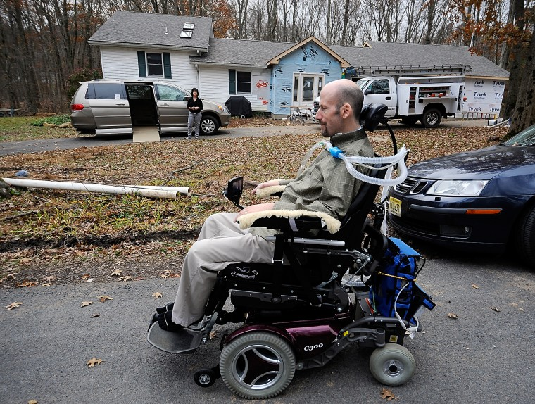 Photo of a wheelchair-bound man with an assisted breathing device, his wife looks on from the background next to a handicap-accessible van