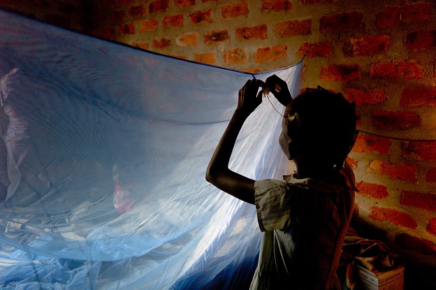 kid installing mosquito netting inside red brick room