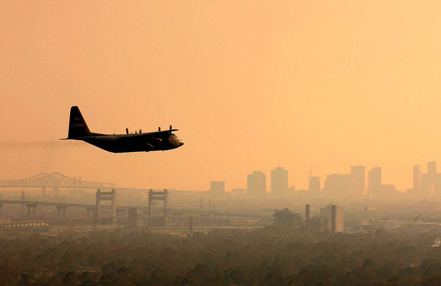 plane spraying insecticide, city skyline in background with orange sky