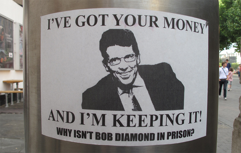 Flyer on a metal pole carries image of a smirking Bob Diamond, reading, 'I've got your money, and I'm keeping it! Why isn't Bob Diamond in prison?'