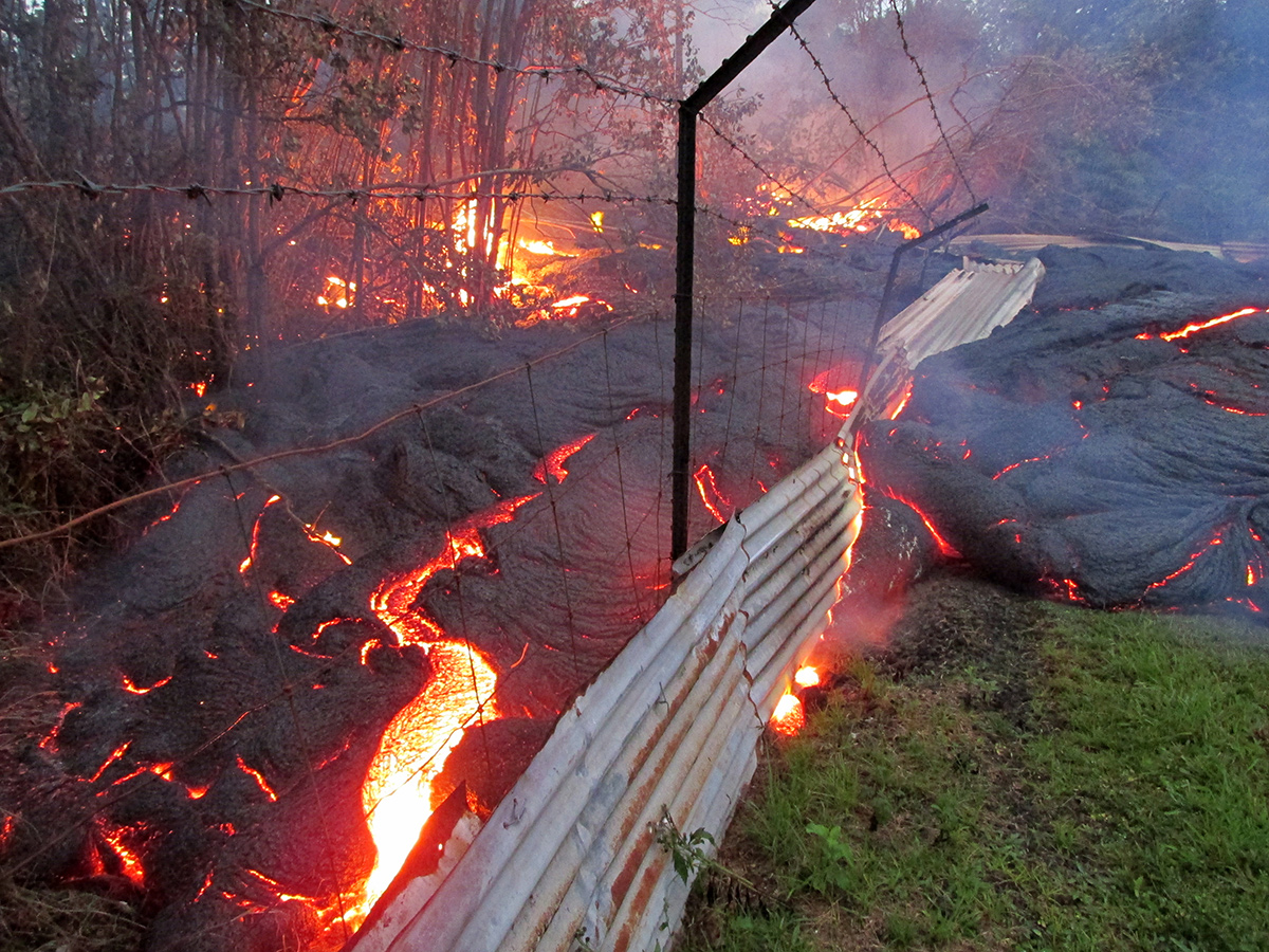bright orange and black crusty-looking lava flows over wire fence
