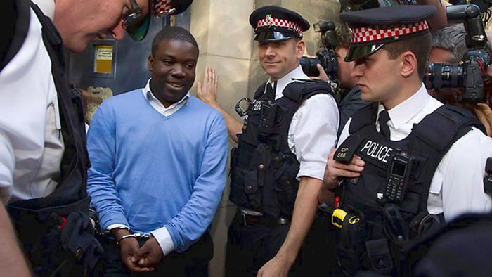 Photo of a smiling white-collar hand-cuffed man escorted from a building by London police officers.