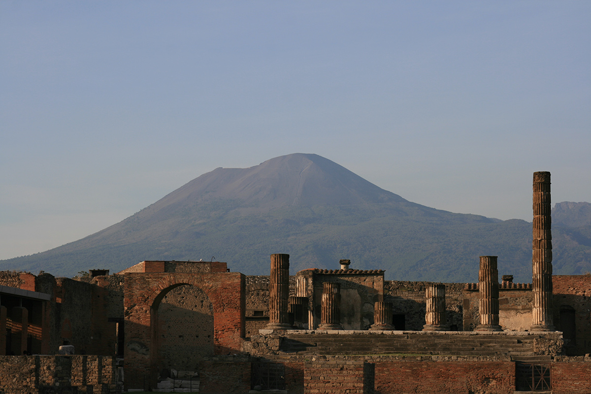 Photo of Roman ruins in late-afternoon light; an immense volcano looms behind.
