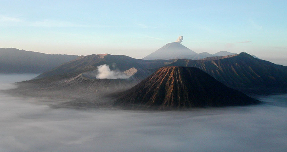 Photo taken above the clouds of a series of enormous volcanic cones and crates; two are spewing smoke.