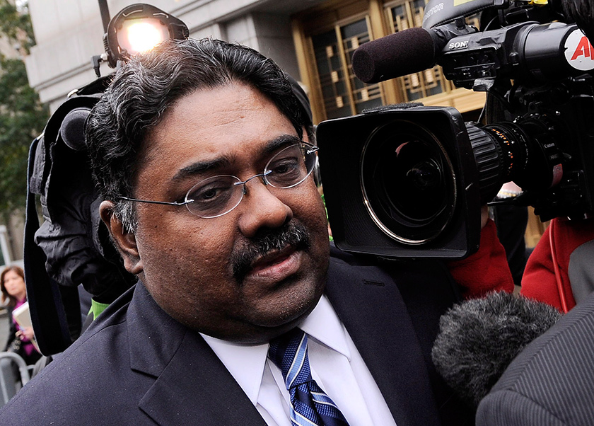 Man-on-the-street -shot of a worried man in a navy suit amid press cameras and reporters.