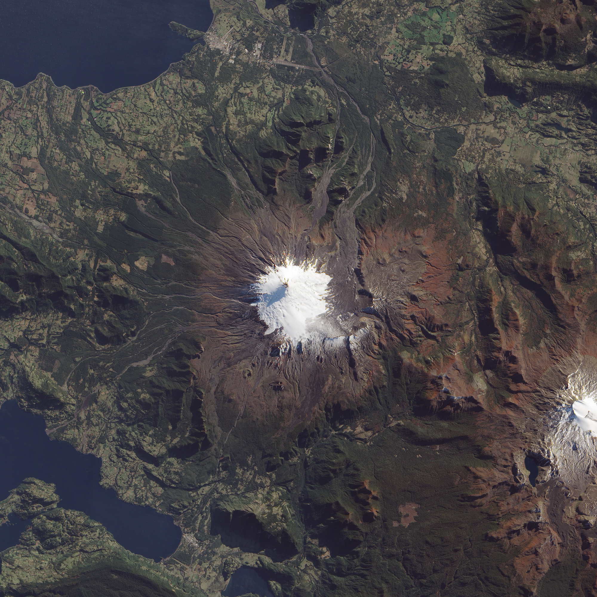 Satellite image looking down on a towering Chilean volcano, topped in snow.