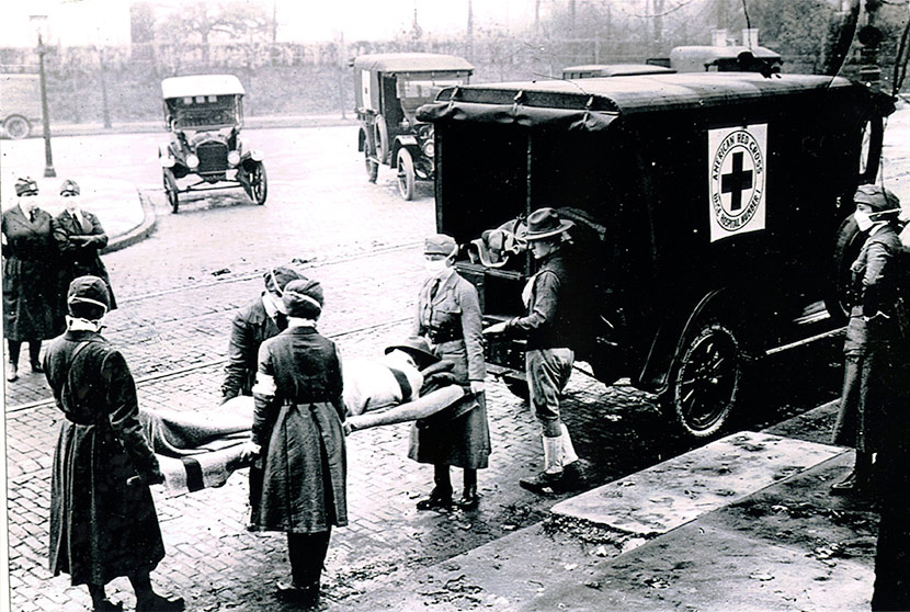 Black and white photograph of nurses donned with surgical masks hefting an infected flu victim on a stretcher into a Red Cross ambulance.