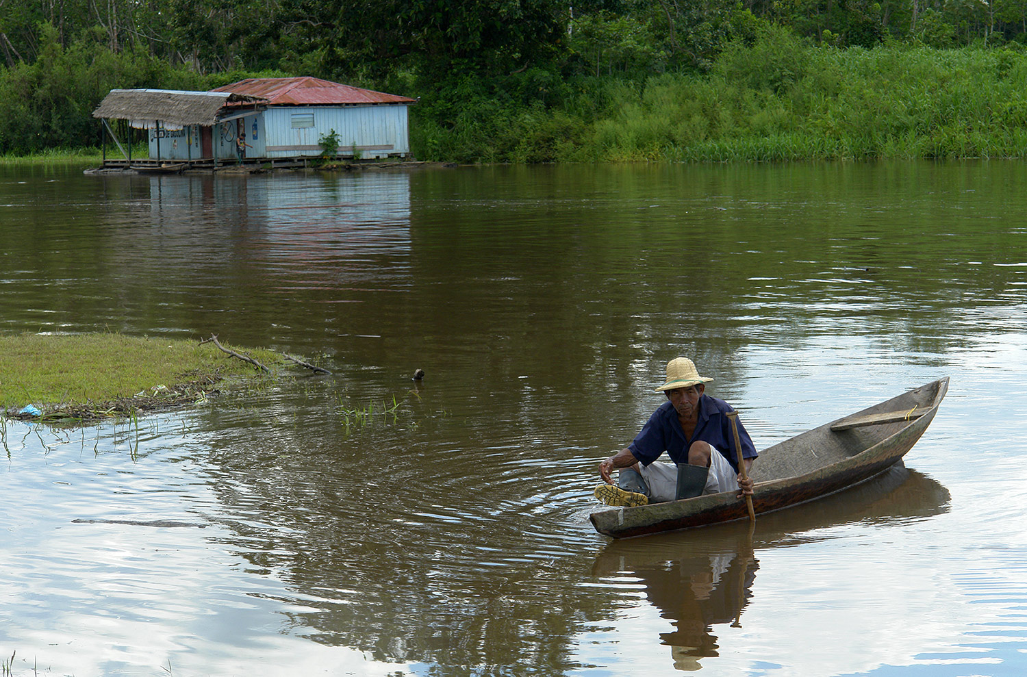 Photograph of an elderly fisherman in a hand-carved canoe floating on the muddy waters of the Amazon.