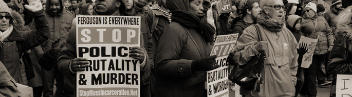 Sepia-toned, detail from: Photograph of several men and women filling an urban street while marching and wielding protest signs