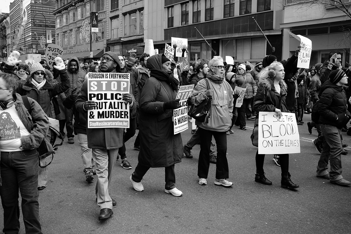 Photograph of several men and women filling an urban street while marching and wielding protest signs.