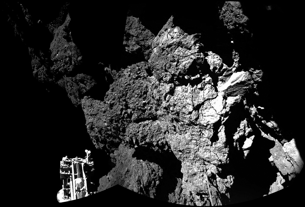 Photo taken from the Rosetta orbiter of the Philae lander on the distant comet before the orbiter lost visual contact. The lander sits in front of a looming and scraggy cliff.