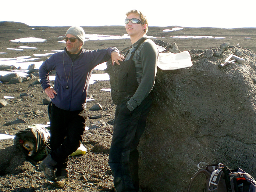 Two glaciologists enjoying the view on an ice-less stretch of the frozen Antarctic dessert.