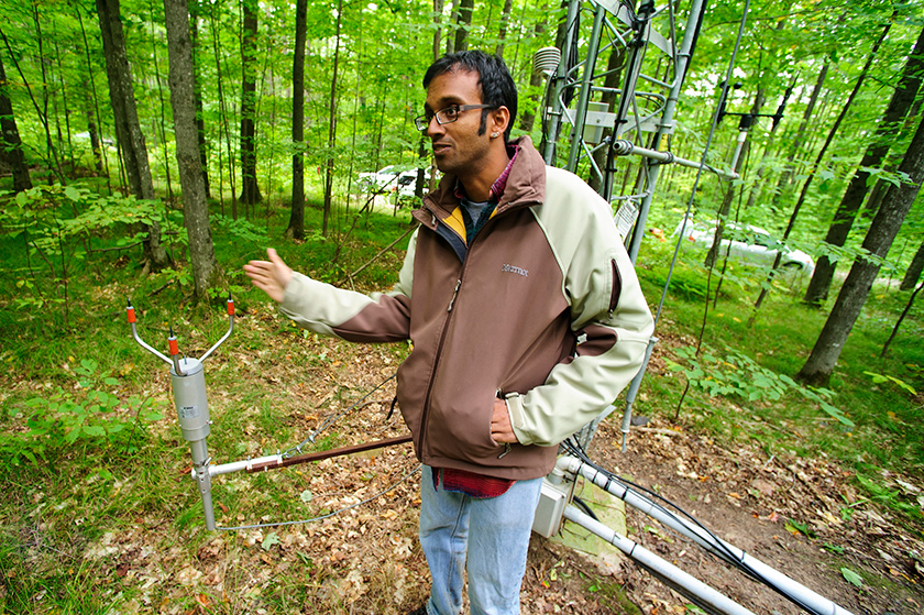 A climate scientist gestures in front of a climate tower in a young forest.
