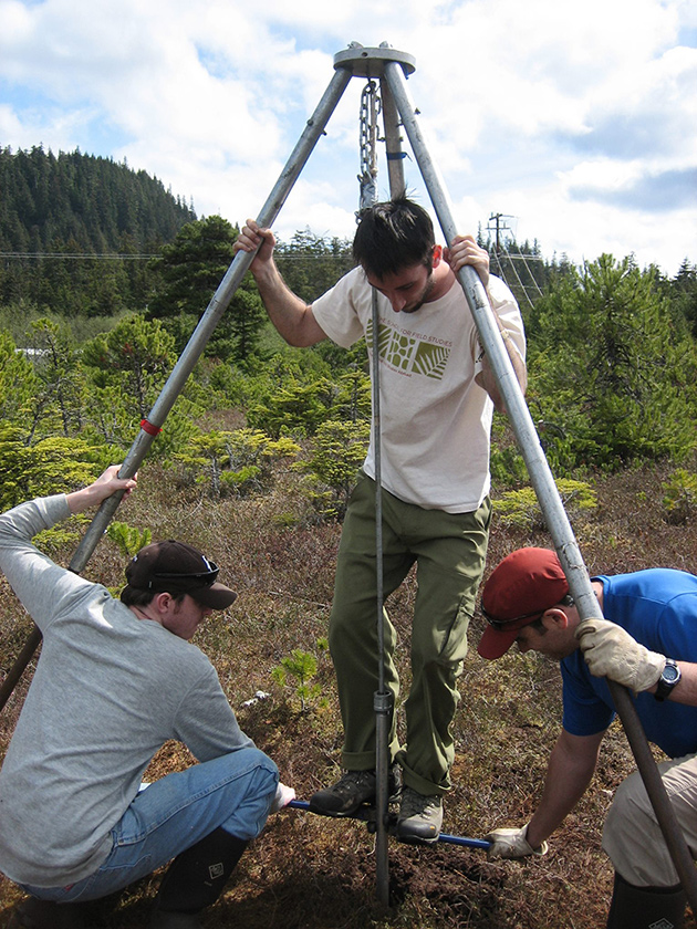 Photo of three researchers using a metal tripod and a steel pipe mechanism to hoist columns of sediment from an Alaskan bog.