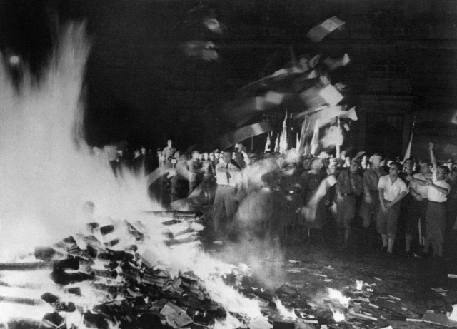 Black-and-white photograph f the famous book burning event in 1933 Berlin showing a crowd of students flinging texts into a blazing fire.