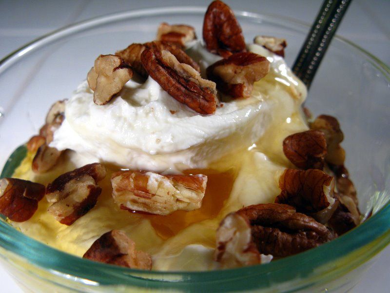 Photo of a well-prepared bowl of yogurt adorned with fresh pecans